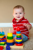 Baby playing with stacking learning toy. Baby boy playing with stacking learning toy Royalty Free Stock Image