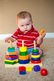 Baby playing with stacking learning toy. Baby boy playing with stacking learning toy Royalty Free Stock Photography