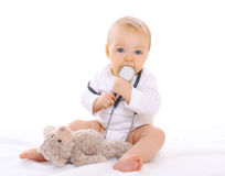 Baby playing with stethoscope and teddy bear Stock Image