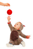 Baby playing stretching hand to Christmas ball Royalty Free Stock Photos