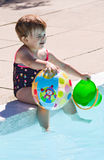 Baby playing in swimming pool water. Cute little baby sitting near swimming pool and playing, summer fun, healthy lifestyle, childhood concept stock images