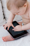Baby playing with tablet. Cute baby with a tablet at home Stock Images