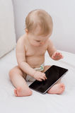 Baby playing with tablet. Cute baby with a tablet at home Royalty Free Stock Images