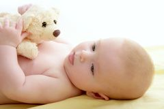 Baby Playing Teddy Bear Laying On Bed Royalty Free Stock Photo