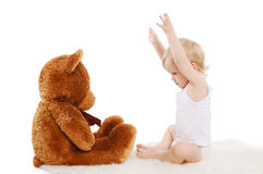 Baby playing with teddy bear Stock Photos