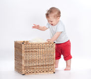 Baby playing with toy in basket on white Stock Photography