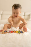 Baby playing toy instrument Royalty Free Stock Photos