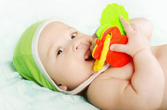 Baby playing with toy. Lying on back Stock Photos