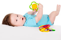 Baby playing with toy. Lying on back Royalty Free Stock Photo