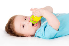 Baby playing with toy. Lying on back Stock Image
