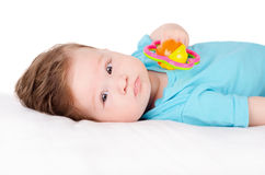 Baby playing with toy. Lying on back Stock Images