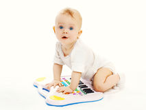 Baby playing with toy piano on white background Royalty Free Stock Photography