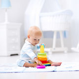 Baby playing with toy pyramid. Kids play Stock Photos