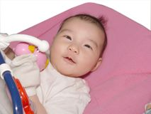 Baby playing with toys. Baby playing with rattles hanging from rocker Stock Image