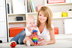 Baby playing with toys with happy mother Royalty Free Stock Photography