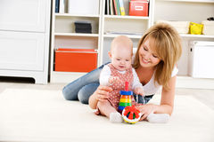 Baby playing with toys with happy mother Stock Image