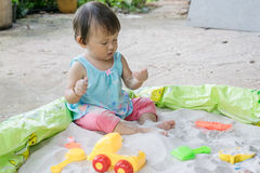 Baby playing toys in sand at home, is fantastic in aiding a toddler s development and it such fun activity to boot Royalty Free Stock Image