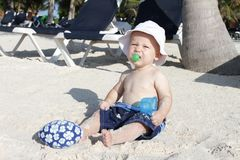 Baby Playing on Tropical Beach. Baby boy playing in sand on a tropical beach Royalty Free Stock Photo