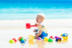 Baby playing on tropical beach digging in sand Stock Photos