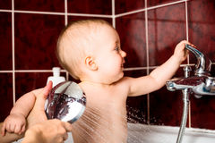 Baby playing with water faucet Stock Image