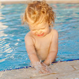 Baby playing with water in swimming pool Stock Image
