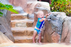 Baby playing with water tap Royalty Free Stock Photography