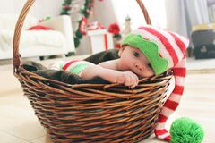 Baby playing in wicker basket Stock Photos