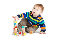 Baby playing with wooden toy cubes with letters. Stock Photos