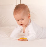 Baby playing with yellow toy Stock Photos