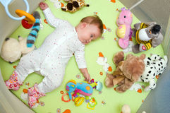 Baby in playpen. Baby girl lying down in colorful playpen with toys Stock Photography