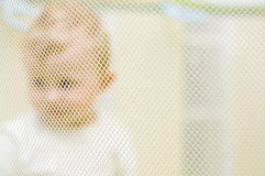 Baby in playpen. Abstract image of a baby behind playpen mesh Stock Photography