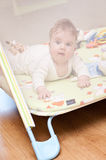 Baby in playpen. Baby girl playing in playpen, seen through the mesh Royalty Free Stock Images