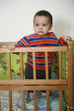Baby in playpen. A view of a cute baby boy standing in a wooden playpen Royalty Free Stock Image