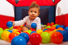 Baby in playpen with balls. Baby boy in playpen playing with balls Royalty Free Stock Photo