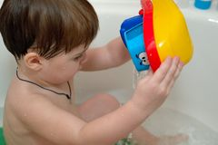 Baby plays in the bath with toy boat Royalty Free Stock Photos