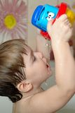 Baby plays in the bath with toy boat Stock Images