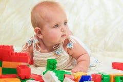 Baby plays with building bricks. Stock Photo
