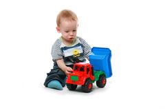 Baby plays with car. Boy child plays with a toy car Royalty Free Stock Photos