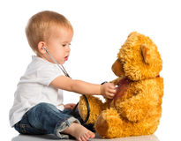 Baby plays in doctor toy bear and stethoscope Stock Image