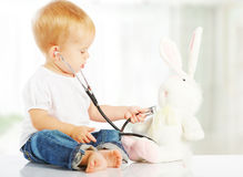 Baby plays in doctor toy bunny rabbit and stethoscope. Cute baby plays in doctor toy bunny rabbit and stethoscope Stock Photo