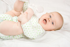 Baby plays with her legs. Six month old baby plays with her oun legs and enjoy in that game Stock Image