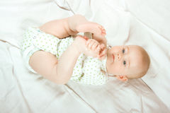 Baby plays with her legs. Six month old baby plays with her own legs and enjoy in that game Stock Photos