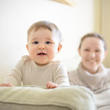 Baby plays with mother on the couch Royalty Free Stock Photography