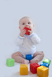 The baby plays with the multi-coloured cubes Stock Image