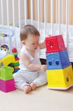 Baby plays nesting blocks at home Royalty Free Stock Photos