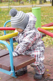 Baby plays outdoors in autumn on playground Royalty Free Stock Photography