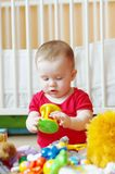Baby plays rattle against white bed Stock Image