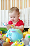 Baby plays rattle against white bed Stock Photos