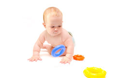 Baby plays with rings. Little baby crawling on the floor with a toy ring stock photography