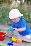 Baby plays with sand. Baby age of 10 months plays with sand Stock Photo